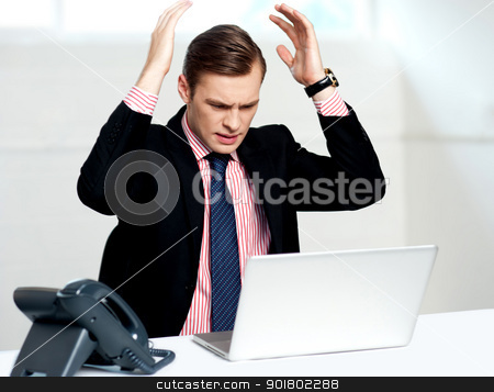 Disappointed businessman looking at laptop stock photo, Disappointed businessman looking at laptop with hands above his head by Ishay Botbol