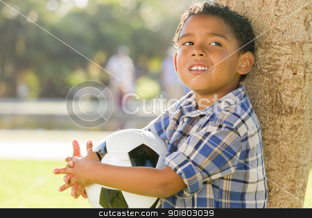 Mixed Race Boy Holding Soccer Ball in the Park stock photo, Mixed Race Boy Holding Soccer Ball in the Park Against a Tree. by Andy Dean