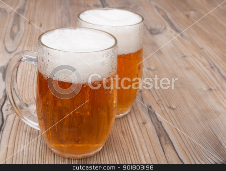Beer Glasses stock photo, Two Glasses of Beer on Aged Wooden Table  by JAMDesign