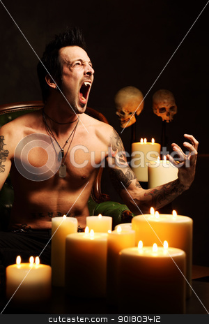 Male vampire showing teeth stock photo, Photo of a male vampire resting in a leather chair and fangs showing.  Harsh and dark lighting for scarier feel. by © Ron Sumners
