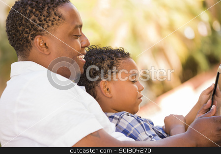 Mixed Race Father and Son Using Touch Pad Computer Tablet stock photo, Happy African American Father and Mixed Race Son Having Fun Using Touch Pad Computer Tablet Outside. by Andy Dean