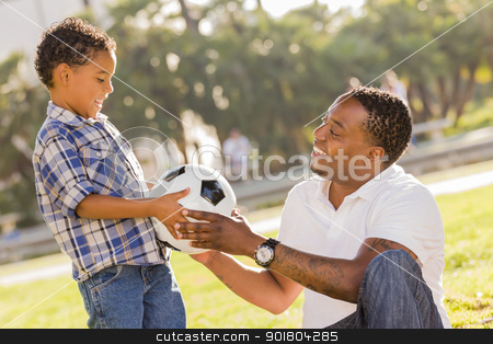 Father Hands New Soccer Ball to Mixed Race Son stock photo, African American Father Hands New Soccer Ball to Mixed Race Son at the Park. by Andy Dean