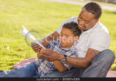 Mixed Race Father and Son Playing with Paper Airplanes stock photo, Happy African American Father and Mixed Race Son Playing with Paper Airplanes in the Park.  by Andy Dean
