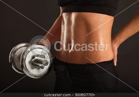 Female lifting a dumbbell stock photo, Photo of the stomach from a sweaty slim female lifting a dumbbell. by © Ron Sumners
