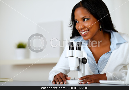 Pretty black woman working with a microscope stock photo, Portrait of a pretty black woman working with a microscope at laboratory by pablocalvog