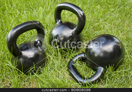 heavy kettlebells in grass stock photo, three heavy iron  kettlebells in green grass - outdoor fitness concept by Marek Uliasz