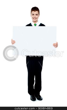 Young boy showing blank billboard stock photo, Young boy showing blank billboard against white background by Ishay Botbol