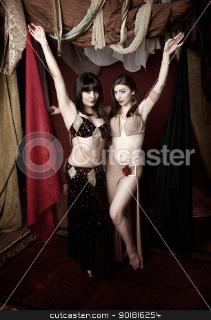 Gorgeous Belly Dancers stock photo, Two gorgeous belly dancers lift up red and black cloths by Scott Griessel