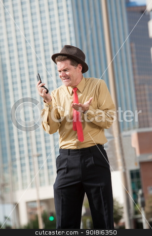 Upset Businessman With Cellphone stock photo, Upset Caucasian businessman with mobile phone on street by Scott Griessel
