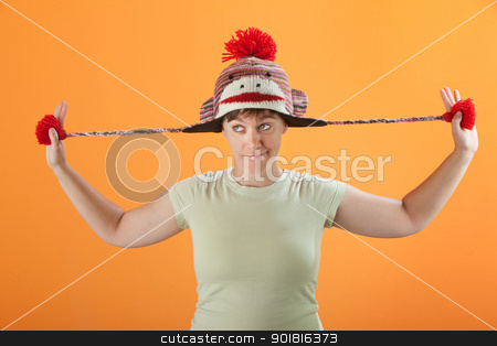 Woman Plays with Her Cap stock photo, Young Caucasian woman fiddles with her sock monkey cap by Scott Griessel