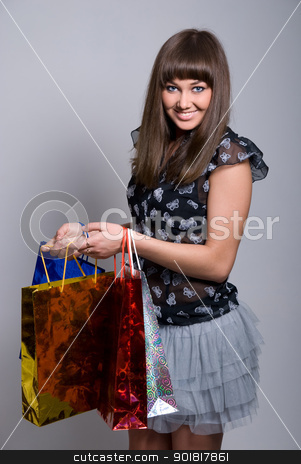 beautiful brunette with packages smiles stock photo, beautiful brunette with packages smiles on a gray background by Vadim