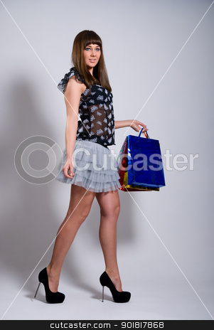 Beautiful girl goes with purchases stock photo, Beautiful girl goes with purchases. by Vadim