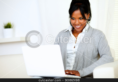 Smiling young woman using laptop stock photo, Portrait of a smiling young woman using laptop while is sitting on sofa at home indoor by pablocalvog