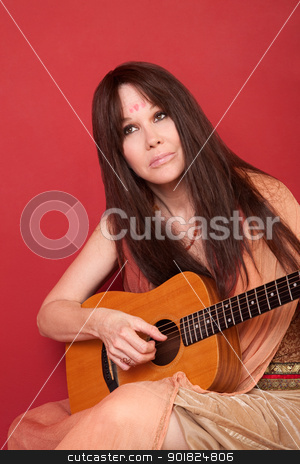 Woman With Guitar stock photo, Woman in Indian outfit holds guitar over red background by Scott Griessel