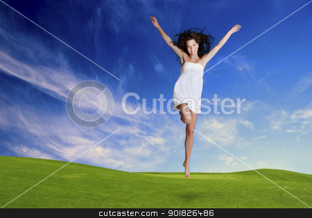 Jumping stock photo, Happy girl jumping in a beautiful green meadow by ikostudio