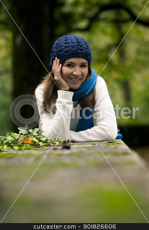 Beautiful young woman in nature stock photo, Outdoor portrait of a beautiful young woman lying on a stonewall by ikostudio