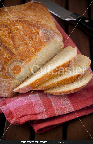 Rustic bread cut into slices stock photo, Baked bread on the wood table with eggs, flour and rolling pin by Giordano Aita