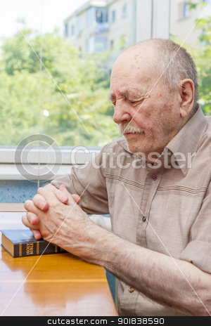 Old man praying stock photo, Old man praying at home near the window by manaemedia