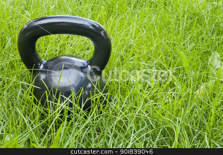 heavy iron  kettlebell in grass stock photo, heavy iron black kettlebell in green grass - outdoor fitness concept by Marek Uliasz
