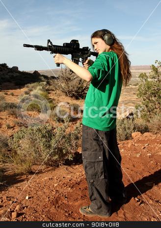 Teenage girl target shooting with rifle. stock photo, Teenage girl shooting at outdoor targets. by asbasb