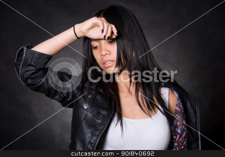Portrait of the tired girl with a hand on a forehead stock photo, Portrait of the tired girl with a hand on a forehead.Asian girl on a black background in a leather jacket by Vadim