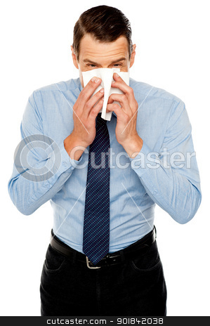 Young man having severe cold. Sneezing stock photo, Young man having severe cold. Sneezing and cleaning nose with tissue paper by Ishay Botbol
