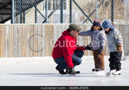 Family having fun at the skating rink stock photo, Family having fun at the outdoor skating rink in winter. by Click Images