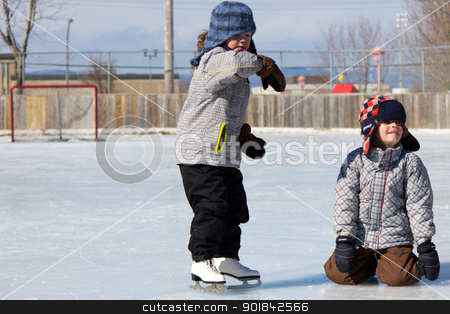 Children at the skating rink stock photo, Children playing and skating at the outdoor skating rink during winter. by Click Images