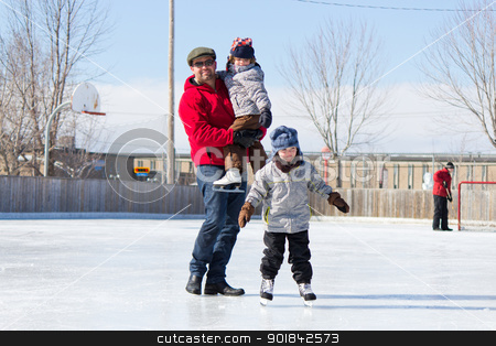 Happy family at the skating rink stock photo, Father with son and daughter playing at the skating rink in winter. by Click Images