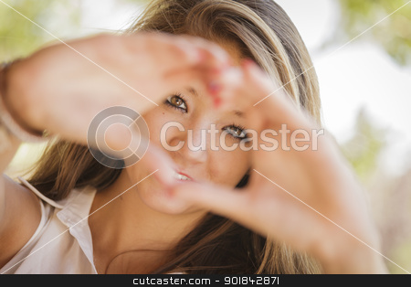 Attractive Smiling Mixed Race Girl Portrait with Heart Hand Sign stock photo, Attractive Smiling Mixed Race Girl Portrait with Heart Hand Sign Outdoors. by Andy Dean