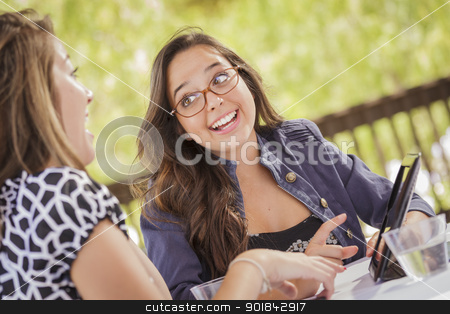 Mixed Race Girls Working Together on Tablet Computer stock photo, Attractive Mixed Race Girls Smiling and Talking While Working on Tablet Computer Sitting Outdoors. by Andy Dean