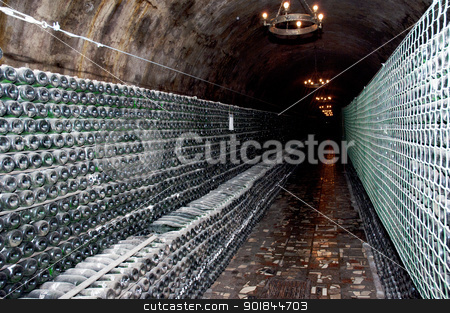 wine bottles in a cellar stock photo, Stack of wine bottles in winery. Shampagne wine storage by Lacroix