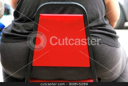 Overweight woman. stock photo, Overweight woman sitting on a small red chair. by OSCAR Williams