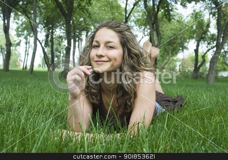 Pretty girl on green field stock photo, portrait of beautiful young woman lying in park  by Aikon
