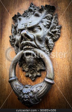 Devil Head Door Knocker stock photo, Door knoker on an old wodden door in Tuscany - Italy by Perseomedusa