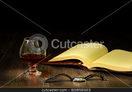 Cognac, cigar and an old book nearby stock photo, A glass with cognac, cigar and an old book nearby by Sergey Nivens