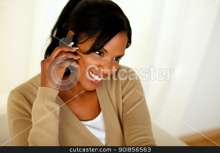 Afro-american woman speaking on mobile phone stock photo, Portrait of an afro-American woman speaking on mobile phone at home indoor by pablocalvog