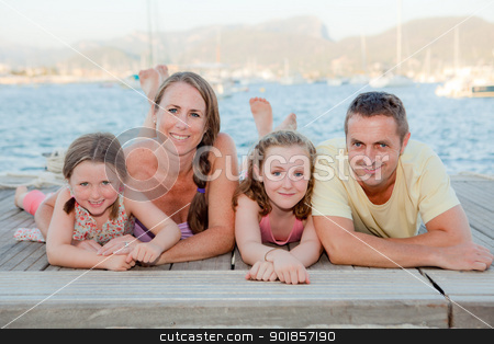 summer family stock photo, summer family smiling laying on beach. by mandygodbehear