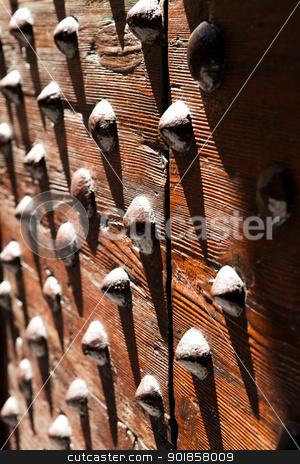Door with studs stock photo, Old wooden door with metal studs by Dario Rota