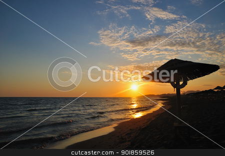 Sunset on beach stock photo, Umbrella on sandy sea beach at sunset stock photo by zagart