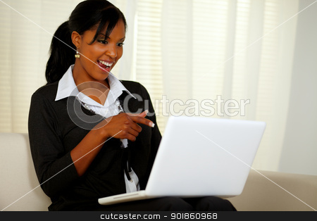 Smiling woman on black suit pointing to laptop stock photo, Portrait of a smiling woman on black suit pointing to laptop screen while sitting on sofa at home indoor by pablocalvog