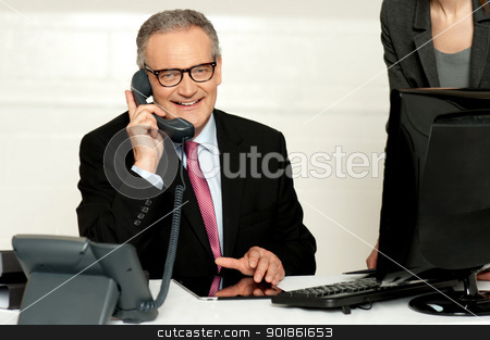 Aged businessman communicating on phone stock photo, Aged businessman communicating on phone with secretary standing beside by Ishay Botbol