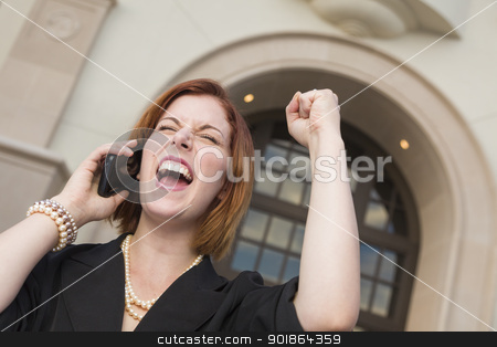 Young Businesswoman with Fist in Air On Cell Phone stock photo, Young Businesswoman with Fist in the Air On Cell Phone in Front of Building. by Andy Dean