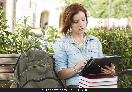 Young Female Student Outside on Bench Using Touch Tablet stock photo, Young Pretty Female Student Outside with Backpack and Books Sitting on Bench Using Touch Tablet. by Andy Dean