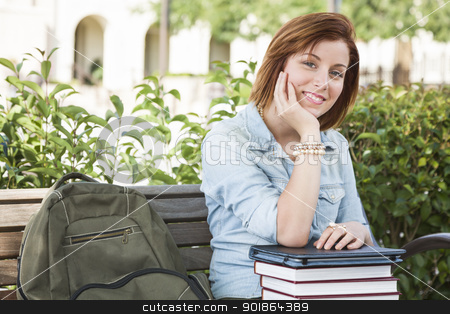 Young Female Student Sitting On Campus with Backpack and Books stock photo, Smiling Young Pretty Female Student Sitting Outside on Bench with Backpack, Books and Touch Tablet. by Andy Dean
