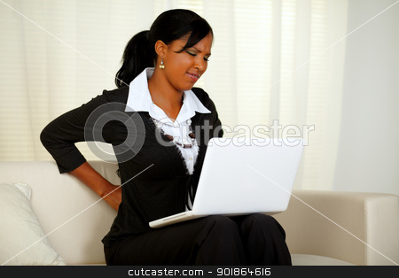 Young businesswoman with back pain stock photo, Portrait of a young businesswoman with back pain that is working on laptop at home indoor by pablocalvog