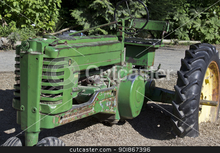 Vintage Tractor 2 stock photo, A vintage green tractor with a large yellow wheel by Jadthree