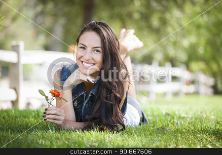 Attractive Mixed Race Girl Portrait Laying in Grass stock photo, Attractive Mixed Race Girl Portrait Laying in Grass Outdoors with Flower. by Andy Dean
