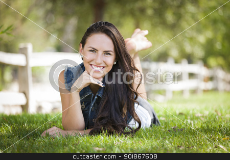 Attractive Mixed Race Girl Portrait Laying in Grass stock photo, Attractive Mixed Race Girl Portrait Laying in Grass Outdoors. by Andy Dean