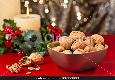 Bowl of walnuts in festive setting stock photo, Bowl of walnuts in festive setting in front of a gold glitter background by Ulrich Schade